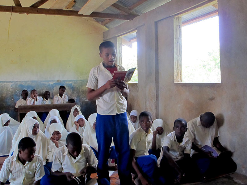 A pupil at Kilindi Nungwi Primary School in Unguja reads aloud to his class. (Photo by Ashleigh Brown of Book Aid International)